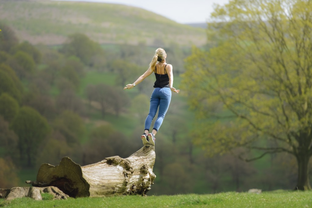 woman-gracefully-falling-jumping-of-tree-in-field